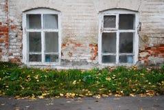 Pared de ladrillo blanca de la casa vieja con dos ventanas de madera con los marcos del vintage pintados en blanco Imagen de archivo