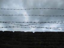 Pared de ladrillo con alambre de púas, contra un cielo nublado oscuro foto de archivo
