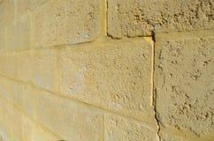 Pared de ladrillo de la piedra caliza con una grieta Imagen de archivo
