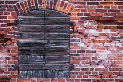 Pared de ladrillo que desmenuza de un almacén alemán viejo con los obturadores cerrados Foto de archivo