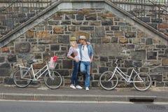 Pared de ladrillo que hace una pausa de los pares jovenes de la cadera con sus bicis Imagenes de archivo