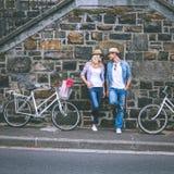 Pared de ladrillo que hace una pausa de los pares jovenes de la cadera con sus bicis Foto de archivo