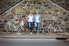 Pared de ladrillo que hace una pausa de los pares jovenes de la cadera con sus bicis Fotos de archivo