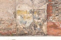 Pared de ladrillo resistida vieja del vintage con yeso y el pavimento quebrados en la tierra Fondo urbano sucio Imagenes de archivo