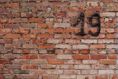 Pared de ladrillo roja con el número 19 Imagen de archivo