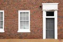 Pared de ladrillo roja con la puerta y las ventanas Foto de archivo libre de regalías