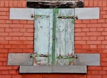 Pared de ladrillo roja con los obturadores de madera foto de archivo libre de regalías
