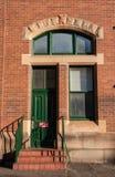 Pared de ladrillo roja con una puerta y una ventana verdes Fotos de archivo libres de regalías