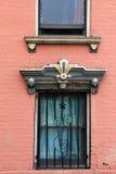 Pared de ladrillo rosada del hogar con las cubiertas viejas, resistidas de la ventana imágenes de archivo libres de regalías