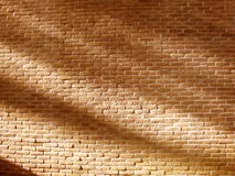 Pared de ladrillo sólida llana del amarillo anaranjado con las sombras del fondo del sol Imagenes de archivo
