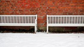 Pared de ladrillo vieja con el banco de dos blancos en invierno Foto de archivo libre de regalías