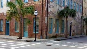 Pared de ladrillo vieja con los posts y las palmeras de la lámpara Fotos de archivo