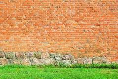 Pared de ladrillo vieja del castillo con la hierba verde en la parte inferior Imágenes de archivo libres de regalías
