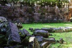 Pared de ladrillo vieja de la ruina en la hierba verde, lugar del viaje imagenes de archivo