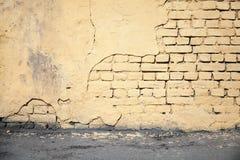 Pared de ladrillo y asfalto dañados amarillo Fotos de archivo libres de regalías