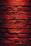 Pared de ladrillo y luz roja en la noche Imágenes de archivo libres de regalías
