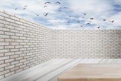 Pared de ladrillo y piso de madera con el cielo azul y las nubes Foto de archivo