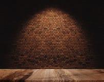 Pared de ladrillo y piso de madera, con el punto ligero en el centro para el fondo imágenes de archivo libres de regalías