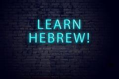 Pared de ladrillo y señal de neón con la inscripción Concepto de aprender hebreo imagen de archivo