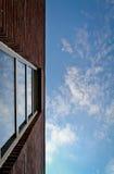 Pared de ladrillo y ventana rojas en cielo Imagenes de archivo