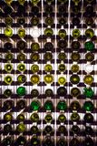 Pared de las botellas de vino vacías Las botellas de vino vacías apiladas-para arriba en otra en modelo se encendieron por la luz imagen de archivo libre de regalías