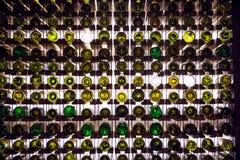Pared de las botellas de vino vacías Las botellas de vino vacías apiladas-para arriba en otra en modelo se encendieron por la luz Foto de archivo libre de regalías