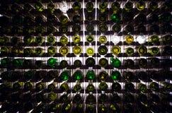 Pared de las botellas de vino vacías Las botellas de vino vacías apiladas-para arriba en otra en modelo se encendieron por la luz Foto de archivo