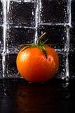 Pared de los cubos de hielo con el tomate de cereza fresco en la tabla mojada negra S Foto de archivo libre de regalías