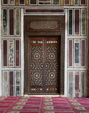 Pared de mármol adornada vieja con una puerta de madera adornada histórica Imágenes de archivo libres de regalías