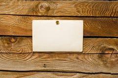 Pared de madera con el papel en blanco para el mensaje Fotografía de archivo