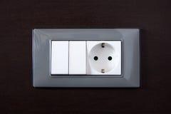 Pared de madera con la toma de corriente y el interruptor de la luz Imagen de archivo