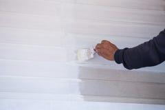 Pared de madera de la pintura del cepillo de la tenencia de la mano Imagen de archivo