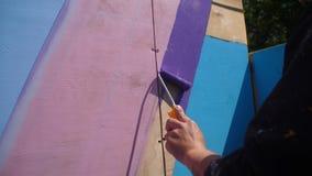 Pared de madera de la pintura femenina de la mano en color azul usando el rodillo de pintura Pintura de la madera con la casa bla Fotografía de archivo libre de regalías