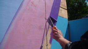 Pared de madera de la pintura femenina de la mano en color azul usando el rodillo de pintura Pintura de la madera con la casa bla almacen de metraje de vídeo