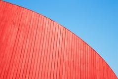 Pared de madera roja de los tablones y cielo azul foto de archivo