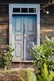 Pared de madera verde con la puerta azul fotografía de archivo