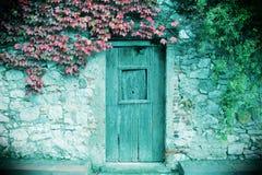 Pared de piedra antigua y un a puerta cerrada de madera imagenes de archivo