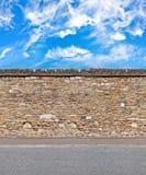 Pared de piedra apilada con los cielos y el modelo inconsútil horizontal del camino de la grava Imágenes de archivo libres de regalías