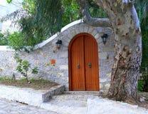 Pared de piedra arqueada de la entrada del patio con la puerta de madera arqueada Foto de archivo