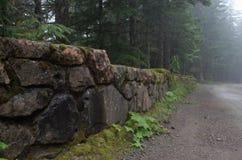 Pared de piedra cerca de árboles imagen de archivo libre de regalías