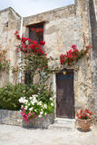 Pared de piedra con la entrada y las flores hermosas Imagen de archivo
