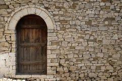 Pared de piedra con la puerta de madera vieja en la ciudad vieja Berat, Albania fotografía de archivo