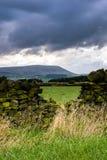Pared de piedra en la granja con la colina de Pendle en distancia en su nublado Fotografía de archivo