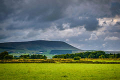 Pared de piedra en la granja con la colina de Pendle en distancia en su nublado Fotografía de archivo libre de regalías