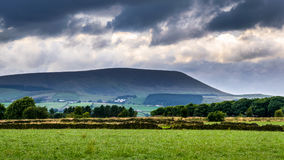 Pared de piedra en la granja con la colina de Pendle en distancia en su nublado Imágenes de archivo libres de regalías