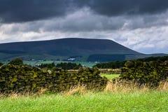 Pared de piedra en la granja con la colina de Pendle en distancia en su nublado Foto de archivo