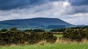 Pared de piedra en la granja con la colina de Pendle en distancia en tarde nublada del verano Foto de archivo libre de regalías