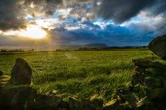 Pared de piedra en la granja con la colina de Pendle en distancia en tarde nublada del verano Imagen de archivo libre de regalías