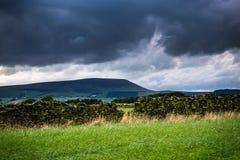 Pared de piedra en la granja con la colina de Pendle en distancia en tarde nublada del verano Fotos de archivo