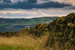 Pared de piedra en la granja con las colinas en distancia en el verano nublado a Fotos de archivo libres de regalías